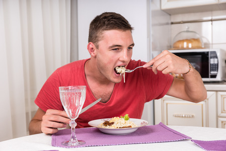 satisfy: Young man eating a plate of spaghetti and meat to satisfy his hunger, with a glass of white wine in the foreground Stock Photo