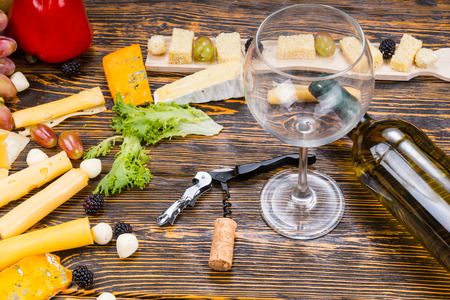 unlabelled: High Angle View of Empty Wine Glass and Bottle of White Wine on Rustic Wooden Table Amongst Gourmet Cheeses and Fruit
