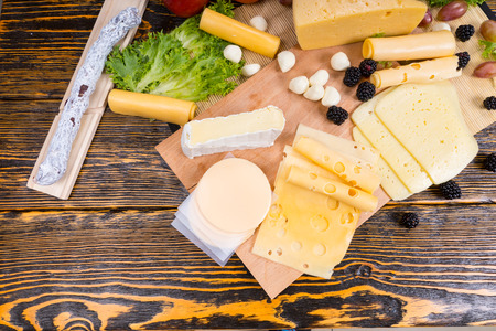 tabla de quesos: Opini�n de alto �ngulo de la Junta de queso gourmet cuenta con variedad de quesos, embutidos y fruta fresca servida en mesa de madera r�stica con madera del grano y el Espacio