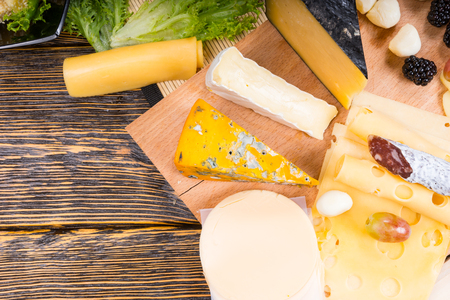tabla de quesos: Vista de �ngulo alto de quesos con variedad de quesos a bordo con Espacio en blanco en la mesa de madera r�stica Foto de archivo