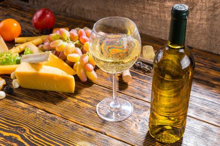 unlabelled: Close Up of Glass and Bottle of White Wine on Rustic Wooden Table with Variety of Cheeses and Grapes with Copy Space in Foreground