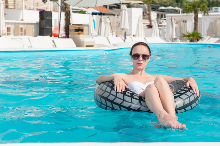 inviting: Pretty woman in a bikini and trendy sunglasses floating in tube on a cool blue inviting swimming pool at a hotel or tropical resort Stock Photo