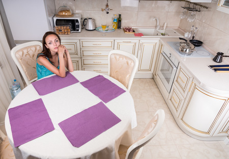 jilted: Pensive Young Woman Sitting at the Table Alone in the Home Kitchen Stock Photo