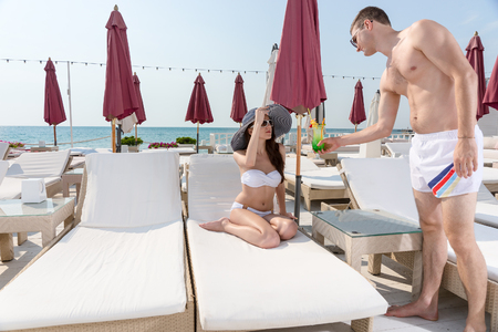 Young Man Serving Tropical Drink to Young Woman Relaxing on Deck Lounge Chair on Sunny Beachfront Luxury Vacation Resort