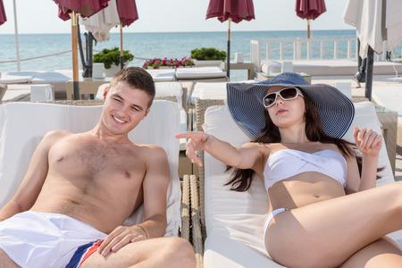 clima tropical: Pareja joven que se relaja en sillones mientras que haciendo unas vacaciones en un Resort en un clima tropical. Foto de archivo