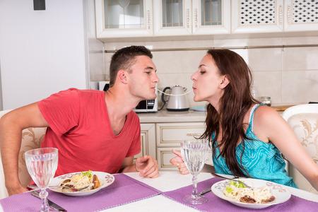 若いカップル一緒に自宅でロマンチックなディナーを持つ男女共有 1 つのスパゲッティ麺キスに近づいて