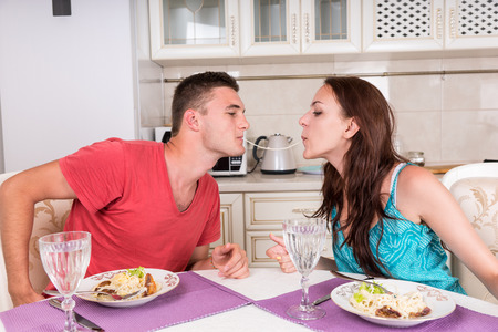 spaghetti dinner: Young Couple Having Romantic Dinner Together at Home - Man and Woman Sharing Single Spaghetti Noodle Getting Closer to Kissing