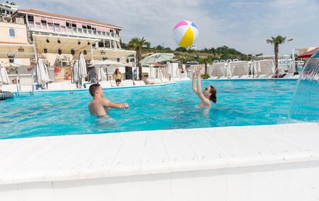 clima tropical: Pareja joven jugando con la pelota de playa en la piscina en un clima tropical.
