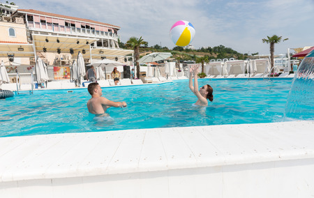 Young Couple Playing with Beach Ball in the Swimming Pool on a Tropical Climate. Stock Photo