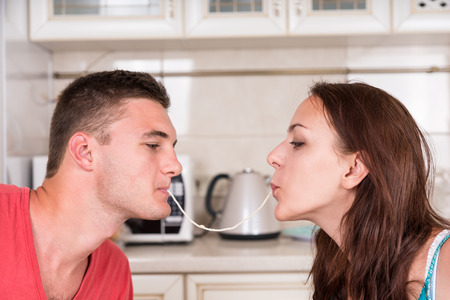 romantico: Perfil de la joven pareja romántica en Dinner Time Sharing sola hebra de espagueti, Slurping juntos hasta que se besan Foto de archivo