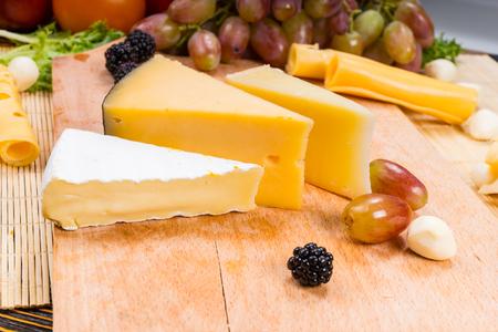 tabla de quesos: Cuñas de una variedad de quesos en una tabla de quesos con uvas frescas, moras y aceitunas para un delicioso buffet de pantalla Foto de archivo
