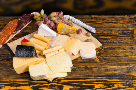 cheeseboard: Delicious cheeseboard on a buffet table with a large selection of different cheeses in wedges displayed with fresh grapes, high angle view with copyspace on a wooden table Stock Photo