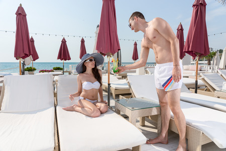 recliner: Young man giving an iced tropical cocktail to his girlfriend as she relaxes in a trendy sunhat on a recliner at a luxury resort on summer vacation