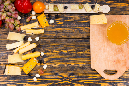 tabla de queso: High Angle View of Ingredients for Cheese Board - Rustic Wooden Table with Cutting Board and Variety of Cheeses and Fruits with Copy Space in Center of Image Foto de archivo