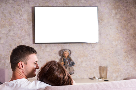snuggling: Rear View of Couple Snuggling Together on Sofa While Watching Flat Screen Television Mounted on Living Room Wall, View of Back of Heads on Romantic Date Night - Screen is Blank for Copy