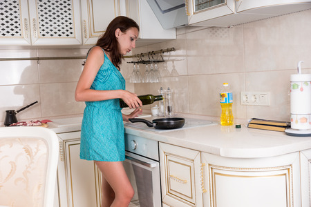 sautee: Young Woman Putting Wine on Frying Pan While Cooking her Favorite Recipe in the Kitchen. Stock Photo