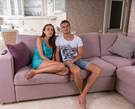 expressionless: Young Couple Sitting Side by Side on Purple Sofa and Watching Television During Relaxing Day at Home