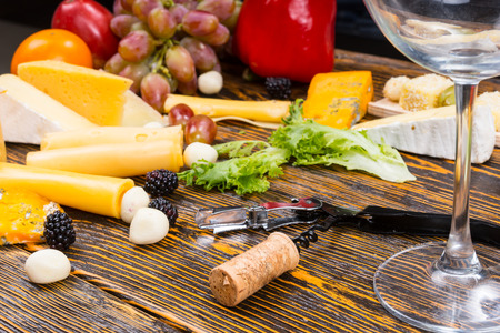 unlabelled: Wine and Cheese Concept Image - Close Up of Empty Wine Glass, Opener and Cork on Rustic Wooden Table Surrounded by Variety of Cheeses and Fruit Stock Photo