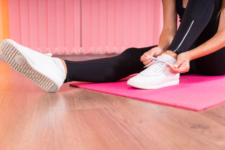 Woman tying the laces of her gym shoes as she sits on a pink yoga or gym mat on a wooden parquet floor preparing for a workout