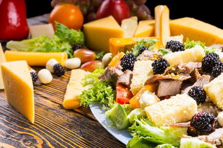 carnes y verduras: Cerca de ensalada gourmet elaborados con verduras frescas, moras, queso y carne en mesa de madera rústica, rodeado por las cuñas de queso y otros ingredientes