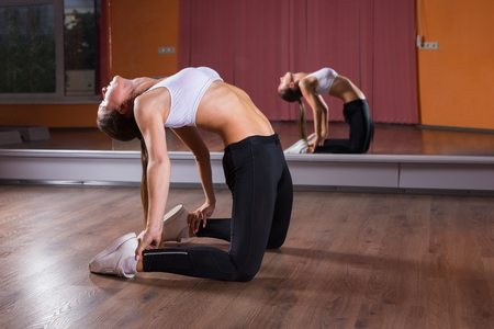suppleness: Full Length Profile of Young Woman Wearing Exercise Clothing Stretching Backwards in Ustrasana Camel Yoga Pose in Dance Studio with Mirrored Wall and Reflection in Background Stock Photo