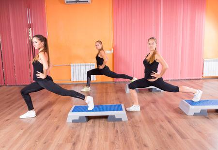 aerobics: Peque�o grupo de tres mujeres j�venes ejercicio juntos en el paso aer�bico clase en moderno y colorido estudio de la danza
