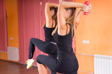 suppleness: Fit Young Girls Holding Dumbbells Behind Their Heads While Balancing with One Leg.
