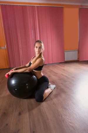 mujer rodillas: Retrato integral de la mujer joven que se arrodilla en el estudio de la danza con los pesos inflable bola del ejercicio y de la mano con espacio de copia