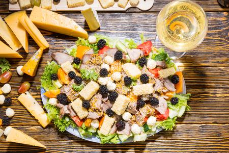 carnes y verduras: Vista elevada de ensalada gourmet elaborados con verduras frescas, moras, variedad de quesos y carnes con ingredientes y copa de vino blanco de mesa de madera rústica Foto de archivo