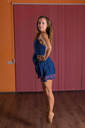 Full Length Side View of a Female Dancer Standing on Tip Toe and Holding her Waist Inside the Studio. Stock Photo