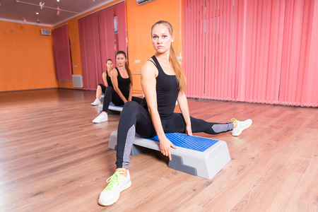 cardiovascular exercising: Small Group of Serious Young Women Stretching Legs on Step Platforms in Step Aerobic Class in Dance Studio with Hardwood Floor and Copy Space