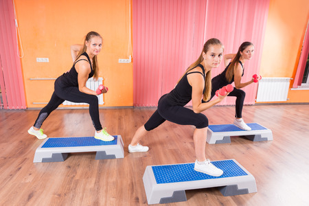 cardiovascular exercising: Three Young Women Doing Indoor Exercise using Dumbbells and Aerobic Steps, Looking at the Camera.