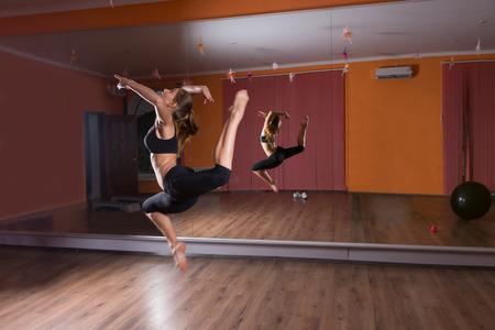 agile: Full Length Profile of Agile Young Female Dancer Leaping in Air in Dance Studio with Mirrored Wall