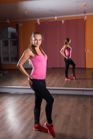 limbering: Full Length Portrait of Young Woman Wearing Exercise Clothing Posing with Hands on Hips in Dance Studio with Mirrored Wall and Looking at Camera Stock Photo