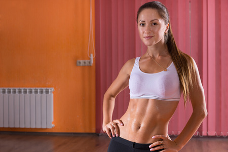 body curve: Portrait of Confident Healthy Brunette Woman Wearing Performance Wear Standing in Dance Studio with Hands on Hips and Smiling at Camera - Woman in Colorful Studio with Copy Space Stock Photo