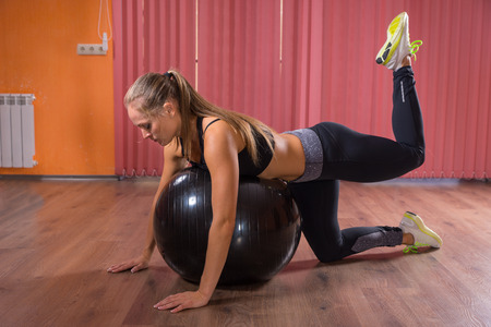 renforcer: Woman doing a pilates workout in a gym using a gym ball to balance on to strengthen and control her muscles, side view on a wooden floor