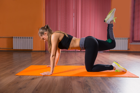 mujer arrodillada: Full Length Side Profile View of Young Blond Woman Kneeling on All Fours on Orange Yoga Mat and Stretching Legs in Exercise Studio