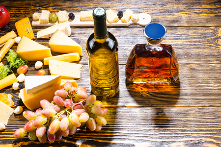 unlabelled: High Angle View of Bottle of White Wine and Amber Whiskey Alcohol on Rustic Wooden Table with Variety of Gourmet Cheese and Grapes - Ingredients for Cheese Board