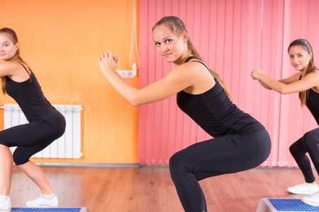 fit women: Three Pretty Fit Women in Squatting Exercise inside the Gym, Smiling at the Camera. Stock Photo