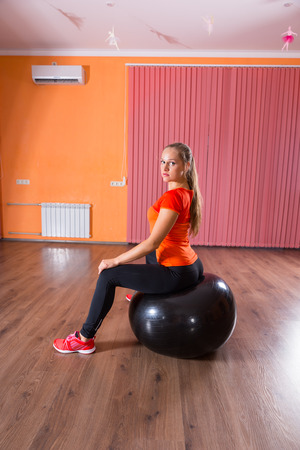 girl sport: Full Length Profile of Young Blond Woman Wearing Exercise Clothing and Sitting on Inflatable Exercise Ball in Dance Studio and Looking Over Shoulder at Camera