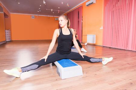 mujeres sentadas: Vista frontal del grupo de mujeres j�venes que estira las piernas en posici�n sentada en plataformas de paso en paso aer�bico clase de colorido Estudio de baile con piso de madera dura Foto de archivo