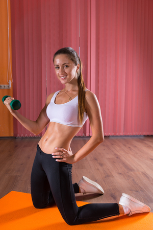 flexed: Healthy fit young woman with a strong toned body lifting a weight in her flexed arms as she kneels on a gym mat in a gymnasium, turning to smile at the camera Stock Photo
