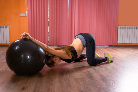 ball stretching: Full Length Side Profile View of Young Woman Wearing Exercise Clothing Stretching on Hardwood Floor Using Inflatable Exercise Ball