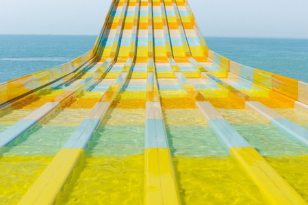 water feature: Colorful water feature slide at a resort or amusement park curving towards the camera with an ocean backdrop