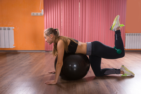 renforcer: Woman doing pilates exercises in a gym balancing across the ball with her leg raised tp strengthen her muscles, side view
