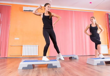 cardiovascular exercising: Low Angle Front View of Pair of Young Women Exercising Together in Step Aerobic Class in Colorful Dance Studio - Step Instructor Teaching Student in Studio Stock Photo