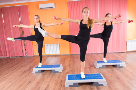 simultaneously: Three Fit Young Women Stretching their Arms and Legs Simultaneously on Top of Fitness Platforms Inside the Gym.