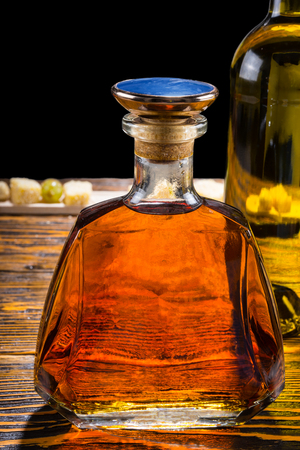 angle bar: Modern stylish glass whiskey decanter with a blue stopper and a wine bottle standing on a wooden table alongside a cheese buffet in the background