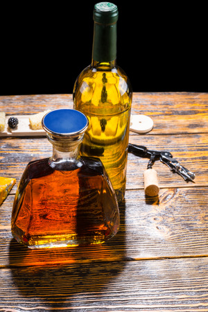 unlabelled: Stylish whiskey decanter and bottle of wine standing on a wooden table with a bottle opener and cork in a pub or bar Stock Photo