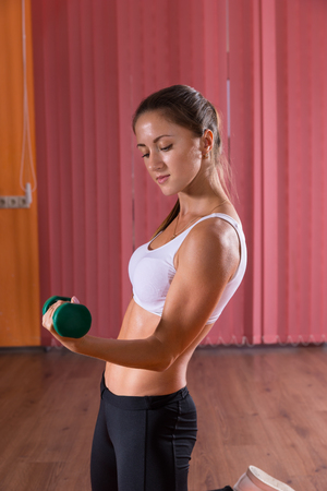cardiovascular exercising: Strong athletic attractive young woman lifting weights in a gym standing sideways flexing her arm while raising the weight in a health and fitness concept